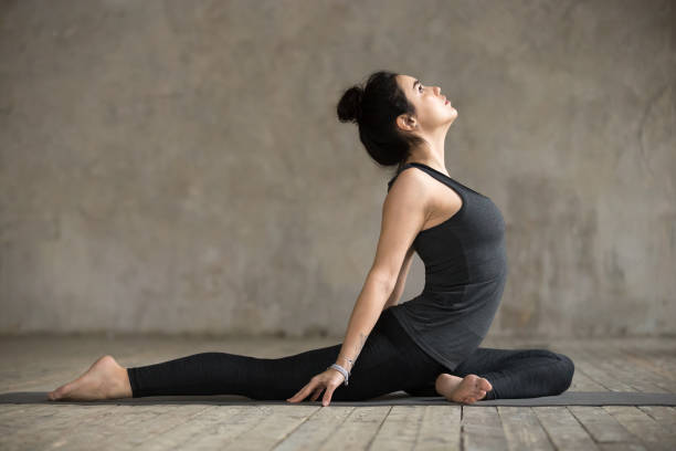 young woman doing single pigeon exercise - yin yang symbol stock pictures, royalty-free photos & images