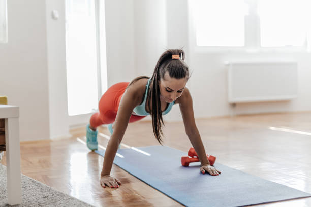 young woman doing some push ups in her living room - milan2099 stock photos and pictures