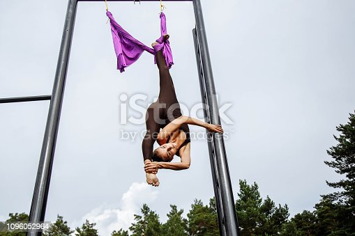 istock Young woman doing splits by using the hammock outdoors. 1096052964