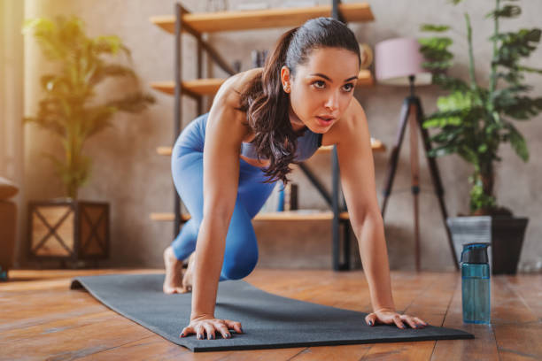 Young woman doing sport exercises indoor at home Young woman doing sport exercises indoor at home yoga mat stock pictures, royalty-free photos & images