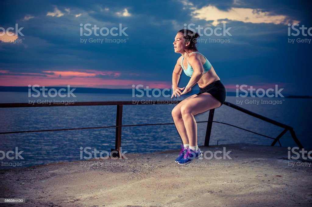 Young woman doing squat jumps on pier stock photo