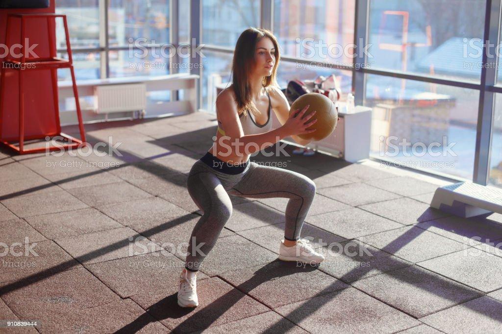 Jeune femme faisant des squats avec médecine-ball en gym - Photo