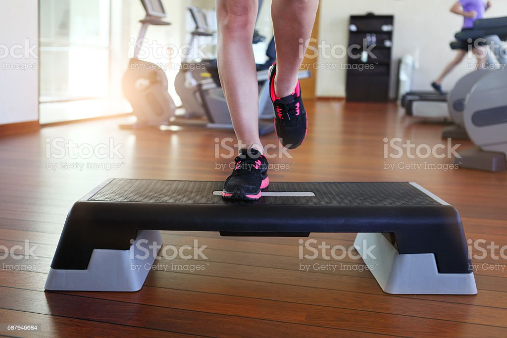 Young woman doing step aerobics while in health club stock photo
