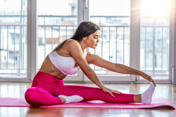 Young woman doing stretching exercises in a health club. Woman on fitness mat doing stretching workout at gym. Young woman doing stretching exercises in a health club. Woman on fitness mat doing stretching workout at gym. touching toes stock pictures, royalty-free photos & images