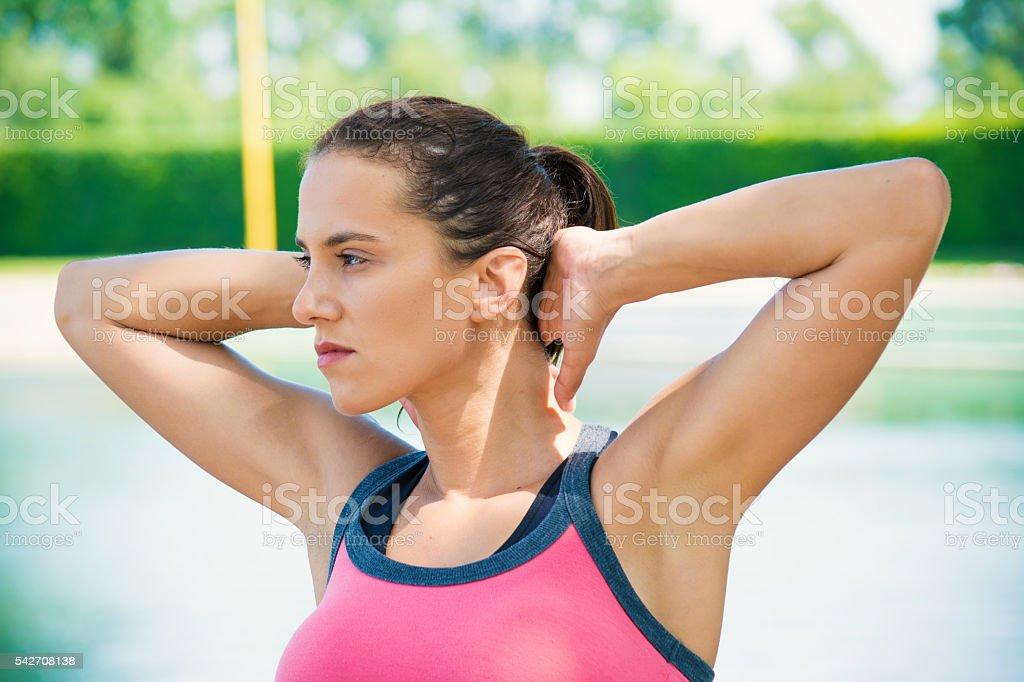Young woman doing stretching workout near lake stock photo