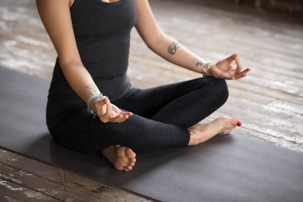 junge frau sukhasana übung, nahaufnahme - buddhist tattoos stock-fotos und bilder