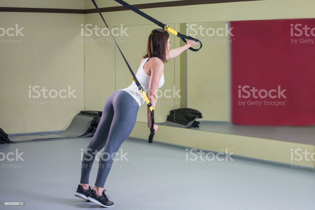 Young woman doing suspension training push-ups with trx fitness straps, side view stock photo