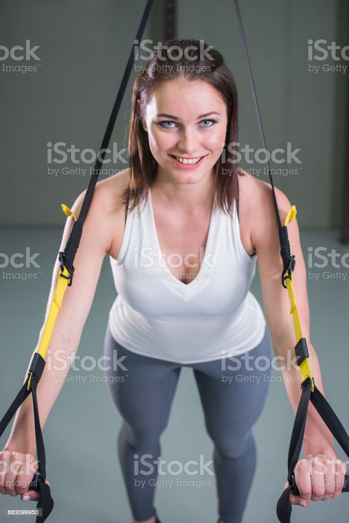 Young woman doing suspension training push-ups with trx fitness straps. stock photo