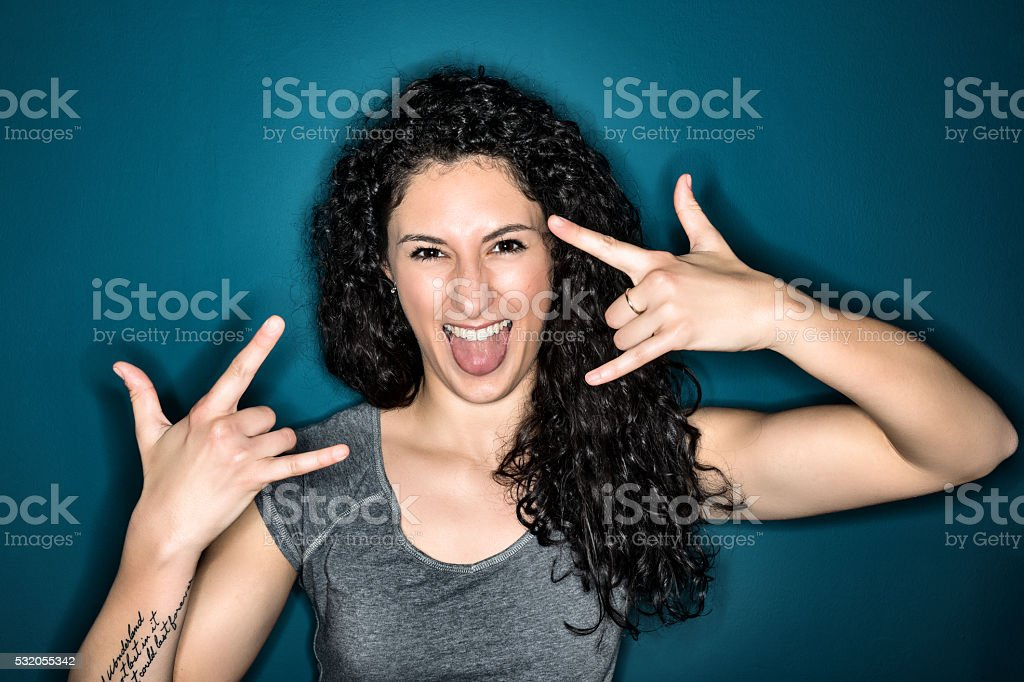 Young woman doing the rock and roll sign stock photo