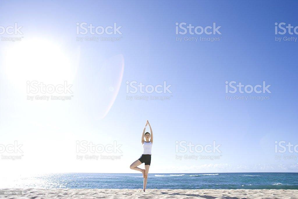 Young woman doing tree pose of yoga asana on beach royalty-free stock photo