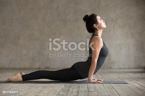 Young woman practicing yoga, doing upward facing dog exercise, Urdhva mukha shvanasana pose, working out, wearing sportswear, black pants and top, indoor full length, gray wall in yoga studio