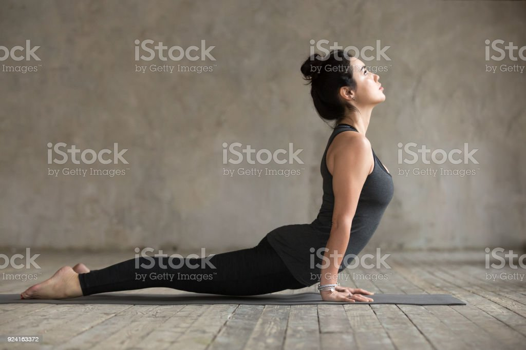Young woman doing upward facing dog exercise stock photo