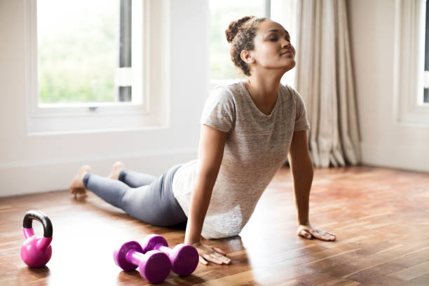 Young woman doing upward facing dog pose at home Young woman doing upward facing dog pose at home. Full length of fit female is exercising on hardwood floor. She is representing healthy lifestyle. sun salutation stock pictures, royalty-free photos & images
