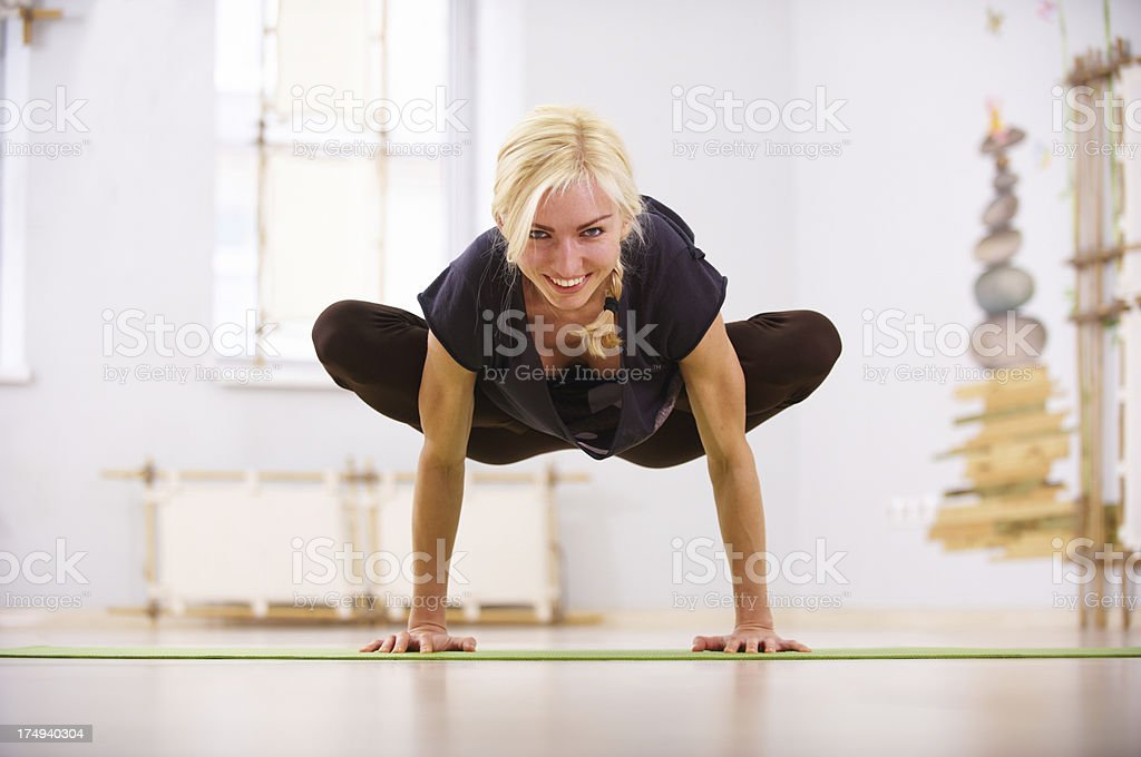 young woman doing urdhva kukkutasana stock photo