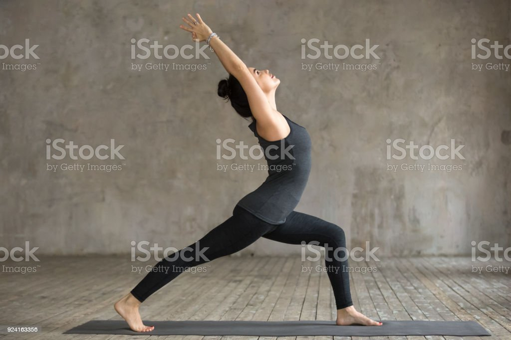 Young woman doing Virabhadrasana 1 exercise stock photo