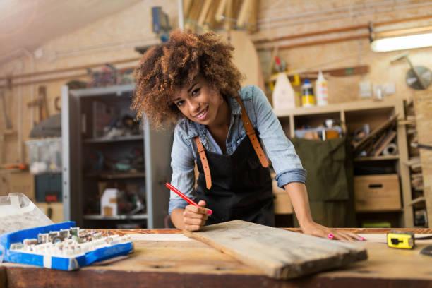 Junge Frau tut Holzarbeiten in einer Werkstatt – Foto