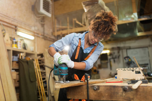 young woman doing woodwork in a workshop - carpenter stock photos and pictures