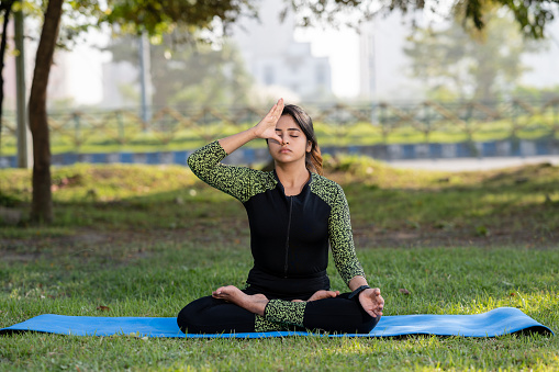 Outdoor image of young Woman doing yoga and Exercise with Pranayama at Park.  Concept of Healthy Yoga and Healthy lifestyle.
