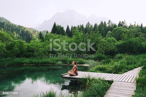 istock Young woman doing yoga and meditating in lotus position on the background of nature. 646072002