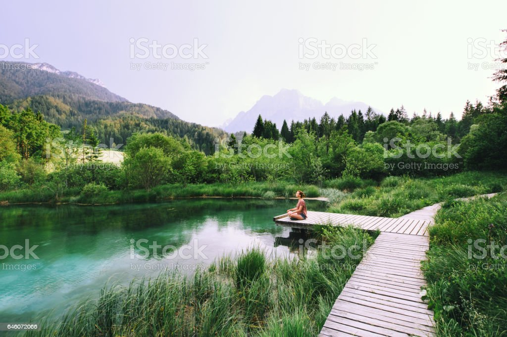 Young woman doing yoga and meditating in lotus position on the background of nature. stock photo