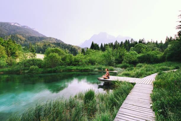 jeune femme faisant le yoga et méditant dans la position de lotus sur l'arrière-plan de la nature. - paysage zen photos et images de collection