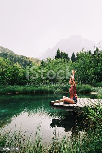 istock Young woman doing yoga and meditating in lotus position on the background of nature. 646072260