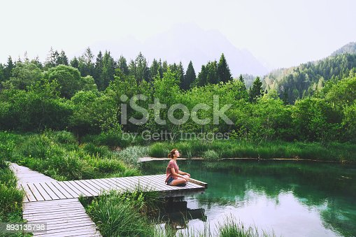 istock Young woman doing yoga and meditating in lotus position on the background of nature. 893135798