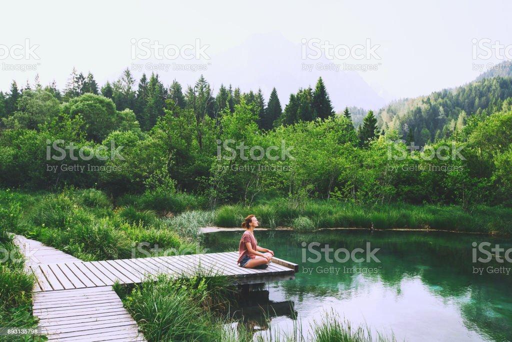 Mujer joven haciendo yoga y meditando en posición de loto en el fondo de la naturaleza. - foto de stock