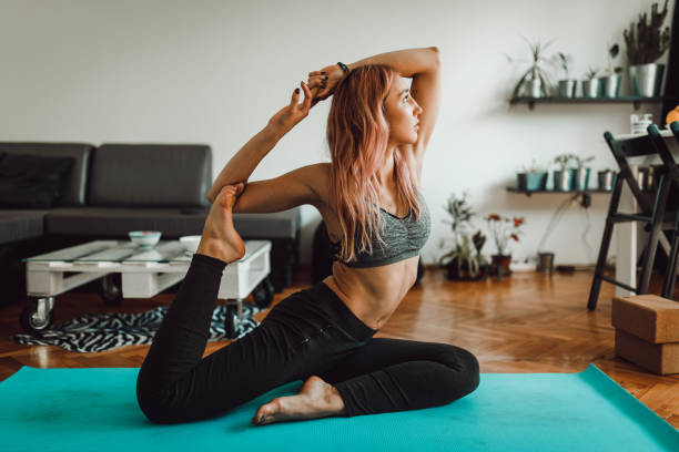 Young woman doing yoga at home stock photo