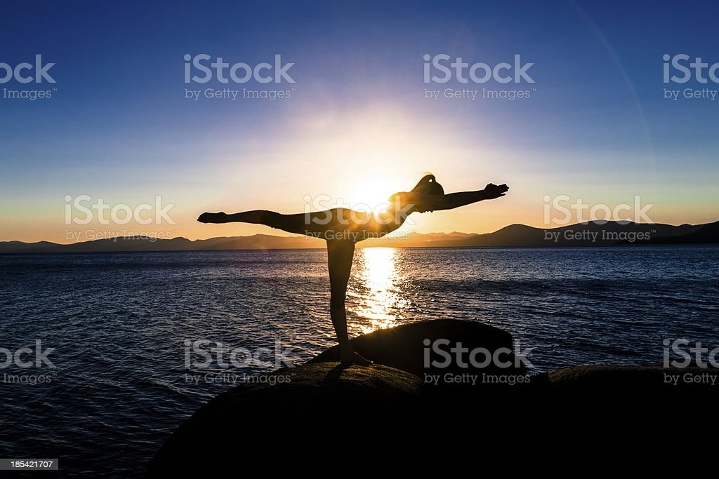 Young woman doing yoga at sunset on Lake Tahoe stock photo