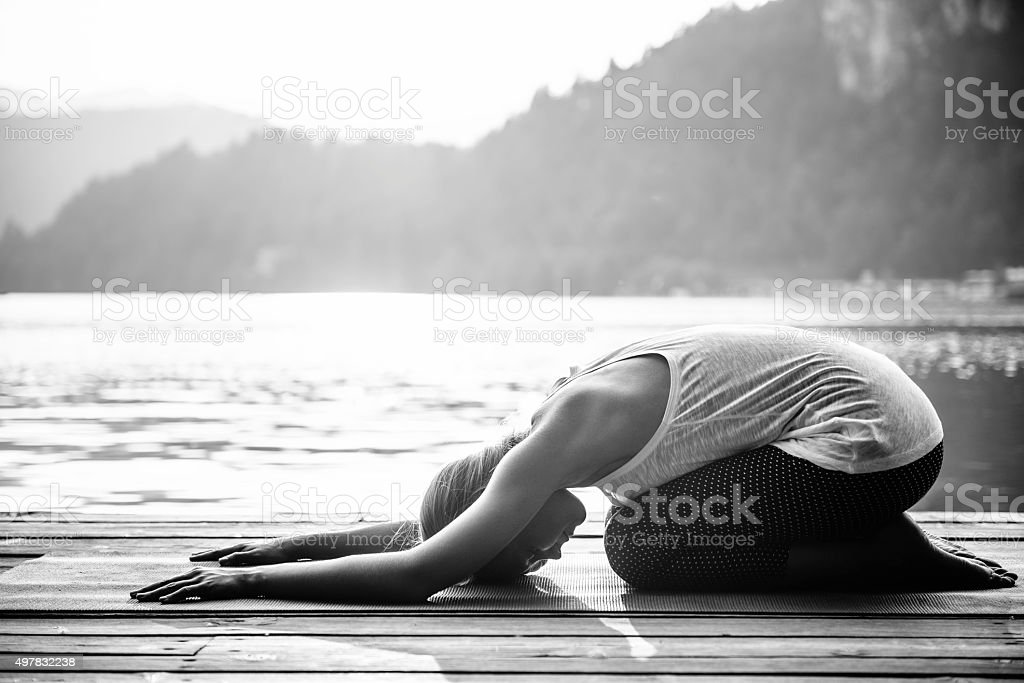 Young woman doing yoga by the lake, childs pose stock photo