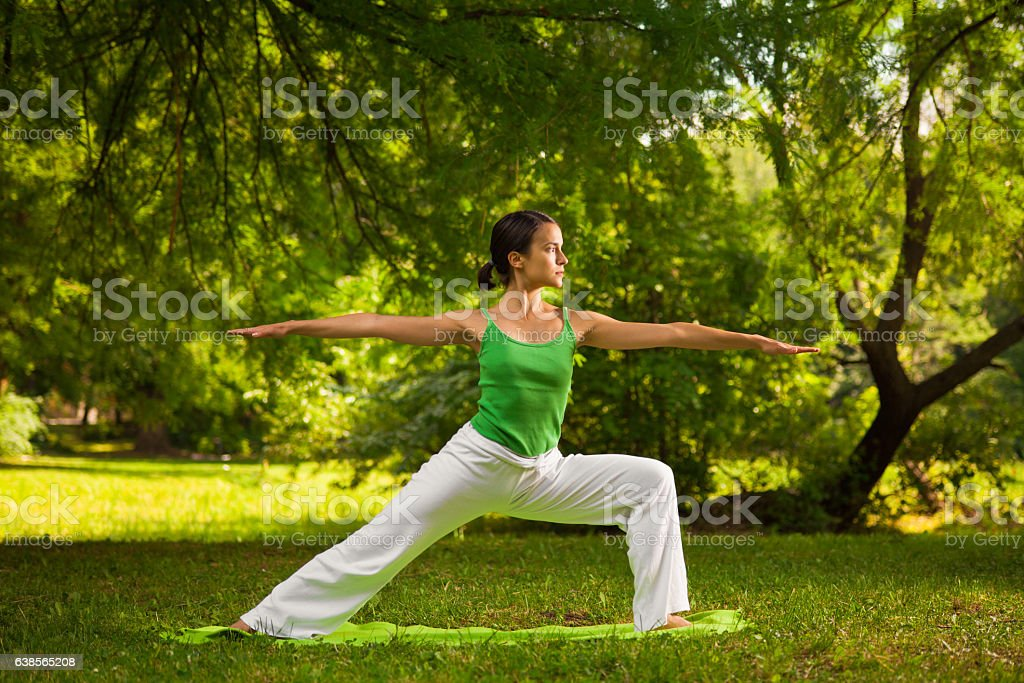 Young woman doing yoga exercise outdoors stock photo