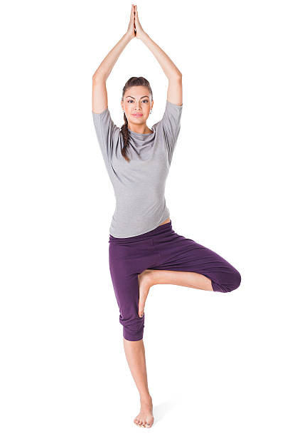 Young woman doing yoga exercise tree-pose isolated on white Young woman doing yoga exercise tree-pose isolated on white background yoga instructor stock pictures, royalty-free photos & images