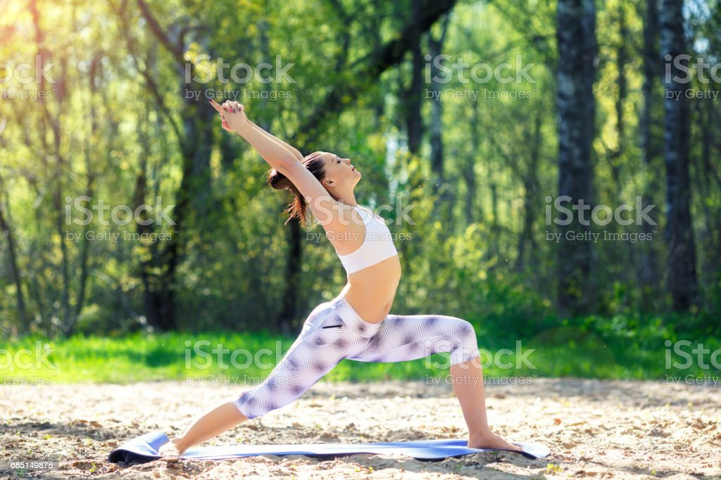 Young woman doing yoga exercises in the summer city park. Health lifestyle concept royalty-free stock photo