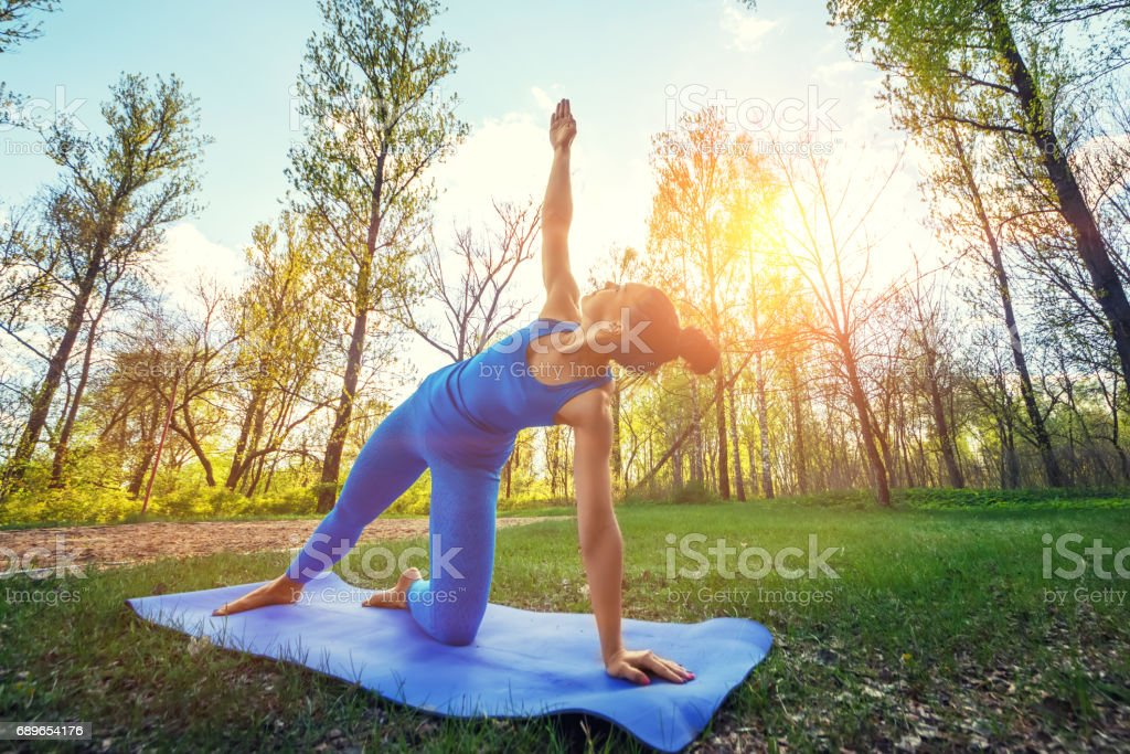 Young Woman Doing Yoga Exercises In The Summer City Park ...