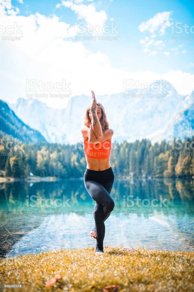 Shot of young woman doing yoga in nature in Slovenia. Mountains and...