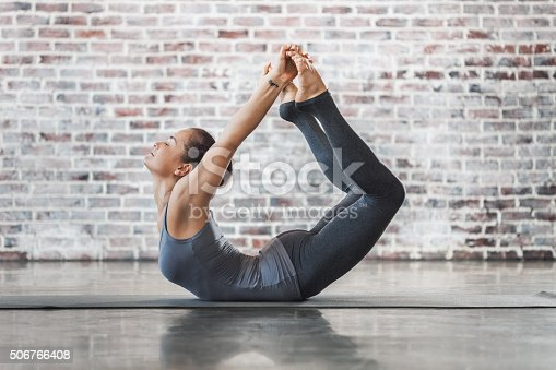 istock Young Woman Doing Yoga Meditation and Stretching Exercises 506766408
