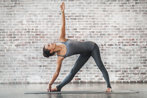Young Woman Doing Yoga Meditation and Stretching Exercises. Triangle Pose. Stock photo.