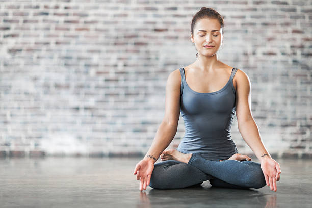 Young Woman Doing Yoga Meditation Exercise. Lotus Position Young Woman Doing Yoga Meditation and Stretching Exercises. Lotus position. Stock photo. lotus position stock pictures, royalty-free photos & images