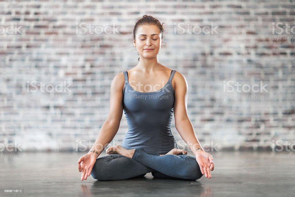 Young Woman Doing Yoga Meditation Exercise. Lotus Position stock photo