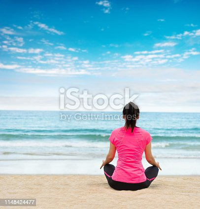 Young woman doing yoga meditation on beach