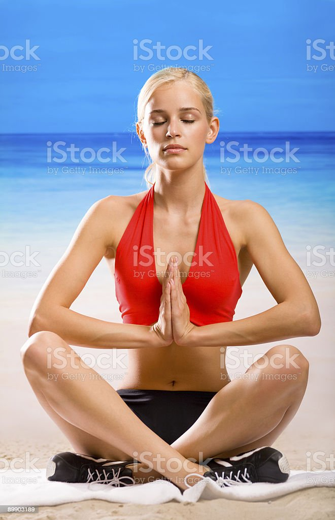 Young woman doing yoga moves or meditating on sea beach royalty-free stock photo