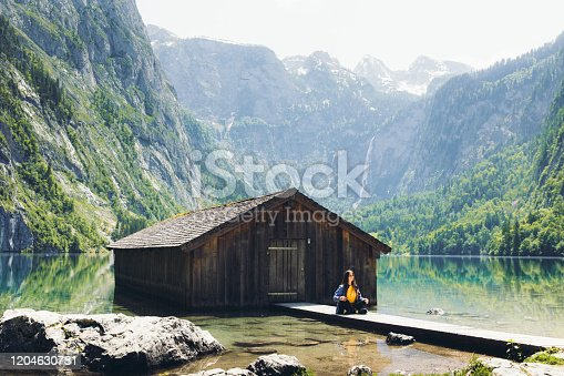 Young woman with long hair feeling awe and happiness meditation and exercising yoga near the abandoned wooden cabin, mountain lake, waterfall and mountains in the Alps, Bayern, Germany