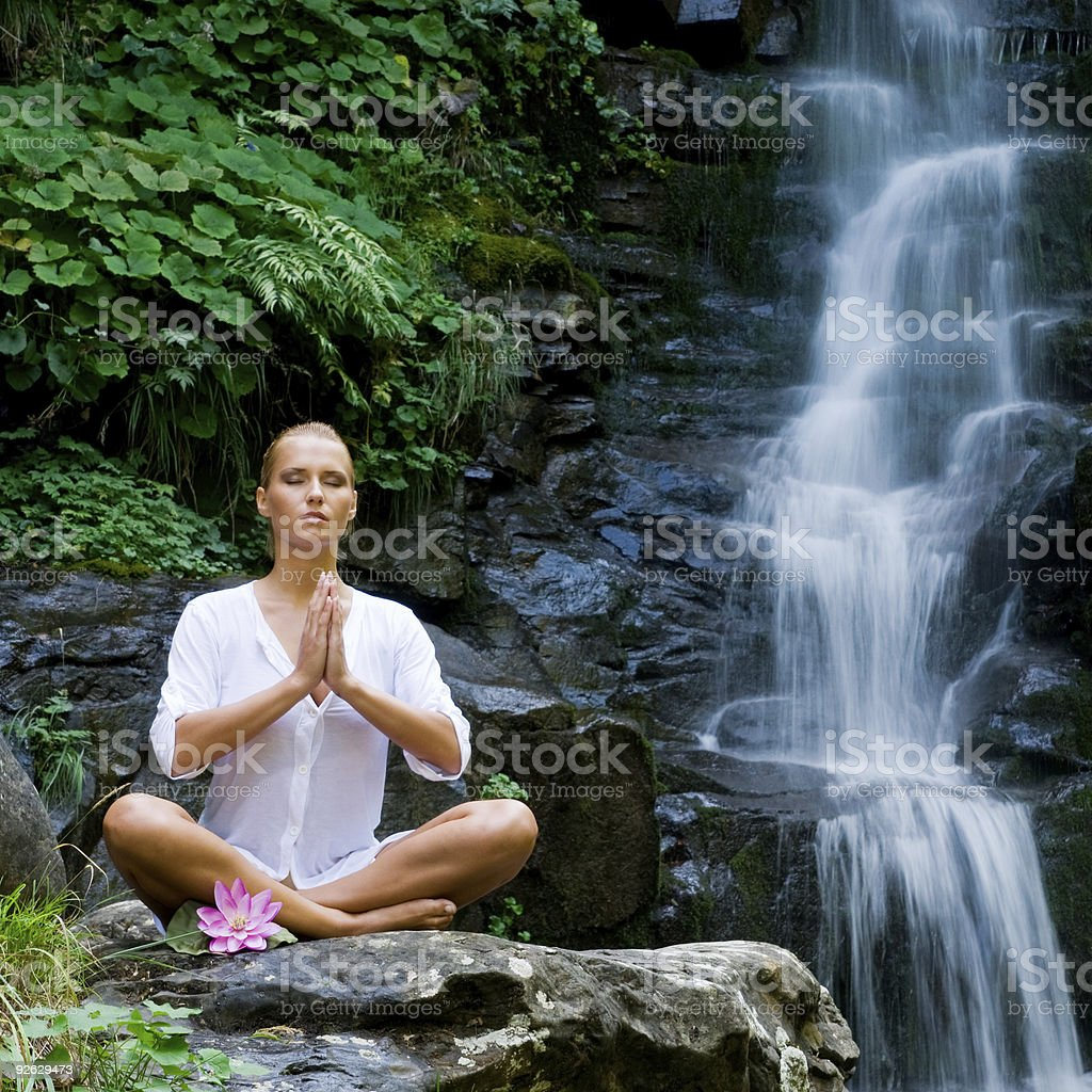 Young woman doing yoga near waterfall royalty-free stock photo