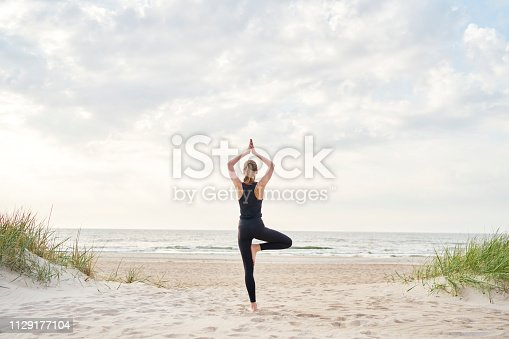 A young woman wearing gym clothes doing yoga on the beach on a sunny day.