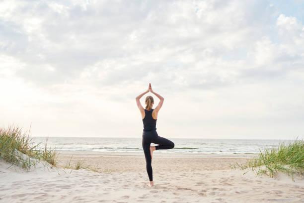 jonge vrouw doet yoga op het strand - yoga stockfoto's en -beelden