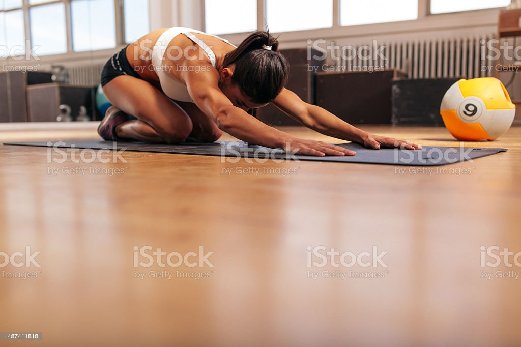 Young woman doing yoga on the gym floor stock photo