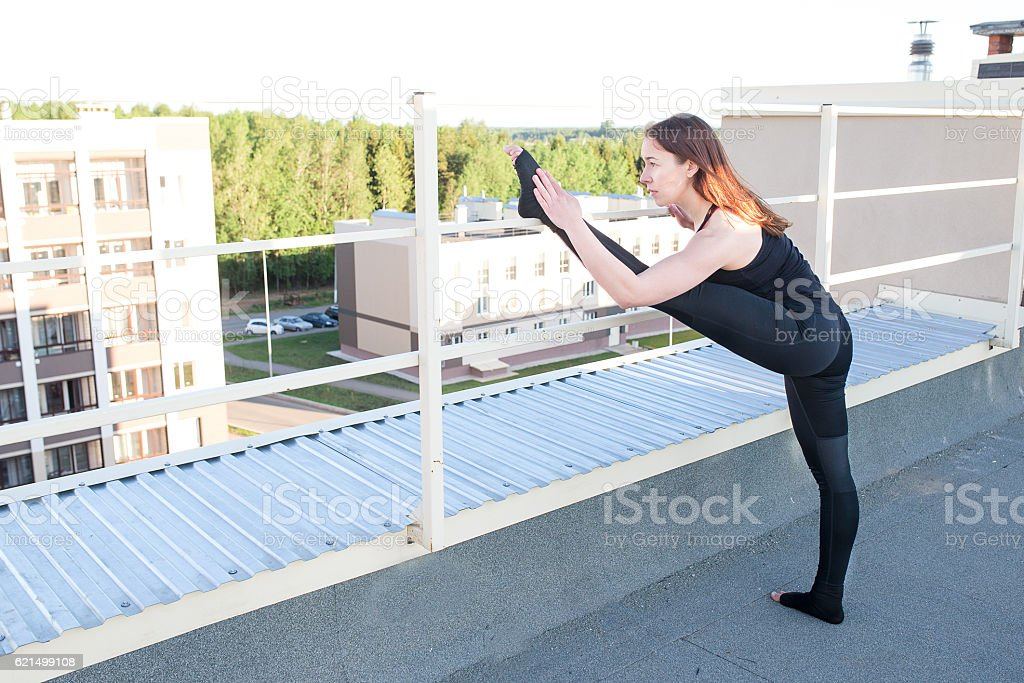 Young woman doing yoga on the roof Lizenzfreies stock-foto