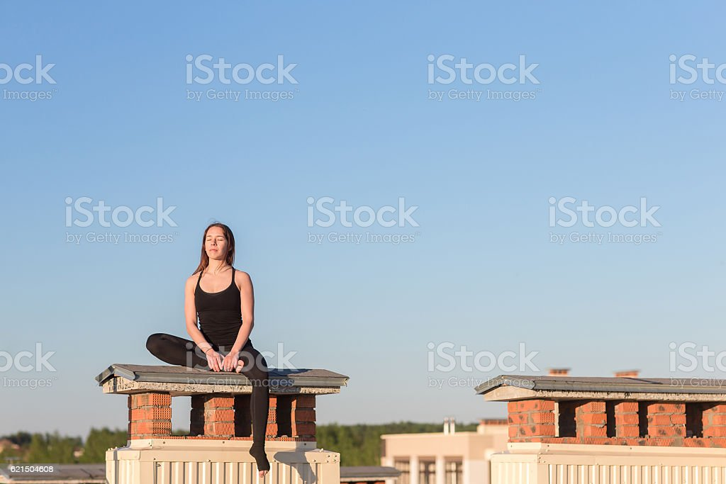 Young woman doing yoga on the roof foto stock royalty-free
