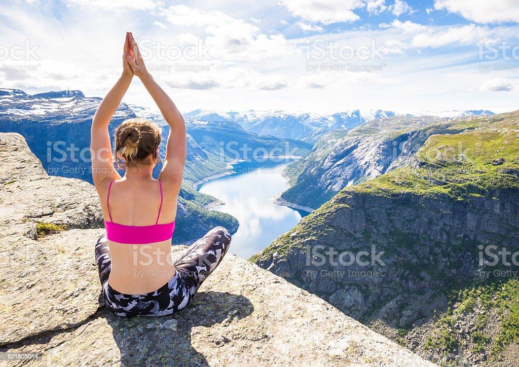 Young woman doing yoga on Trolltunga. Happy girl enjoy beautiful photo libre de droits